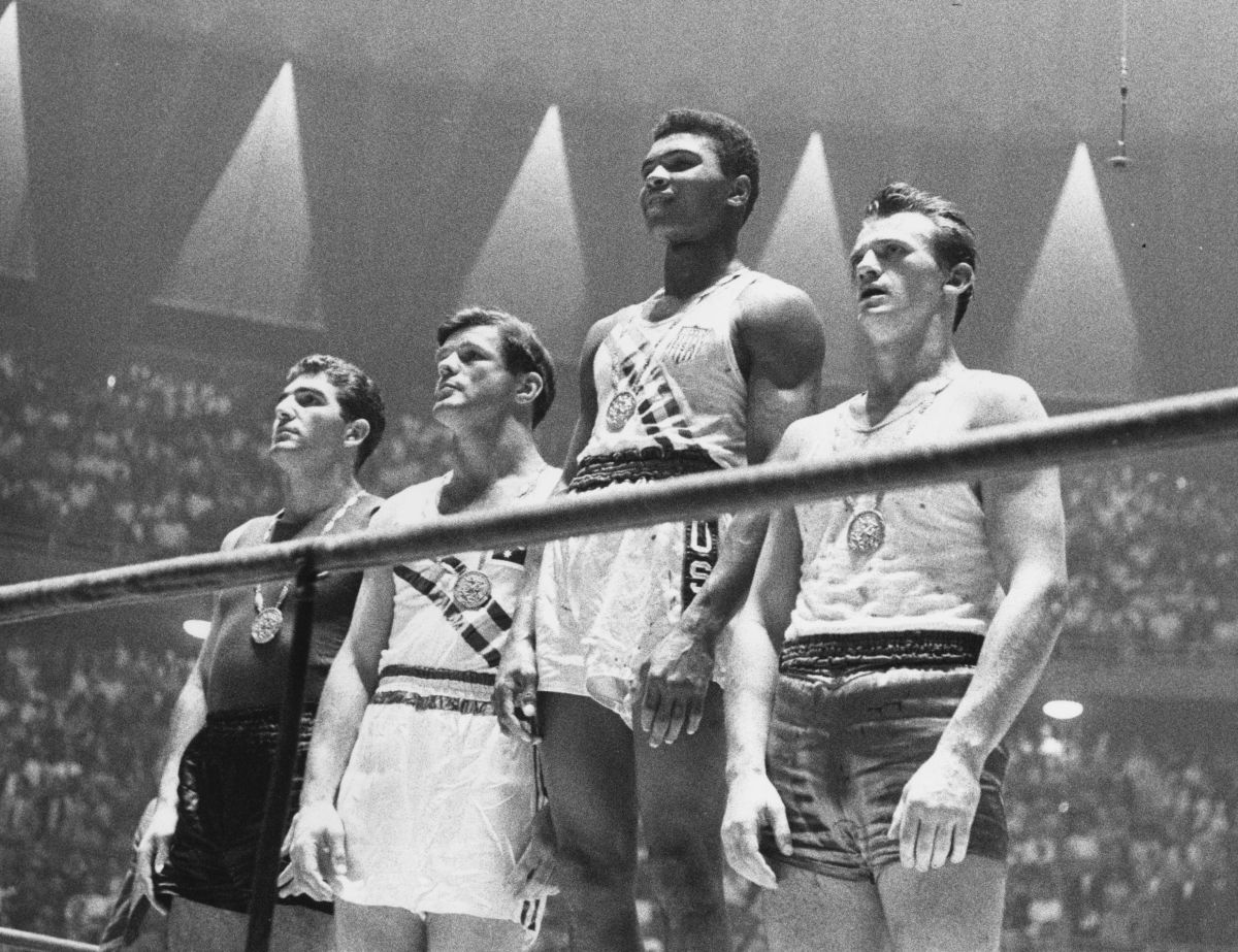 Muhammad Ali: During the 1960 Olympics, Muhammad Ali towers over fellow Olympians Zbigniew Pietrzykowski of Poland (R), Giulio Saraudi of Italy (L)  and Anthony Madigan of Australia (2nd-L) as the gold medalist for light heavyweight boxing.  (Photo by Central  Press/Getty Images)