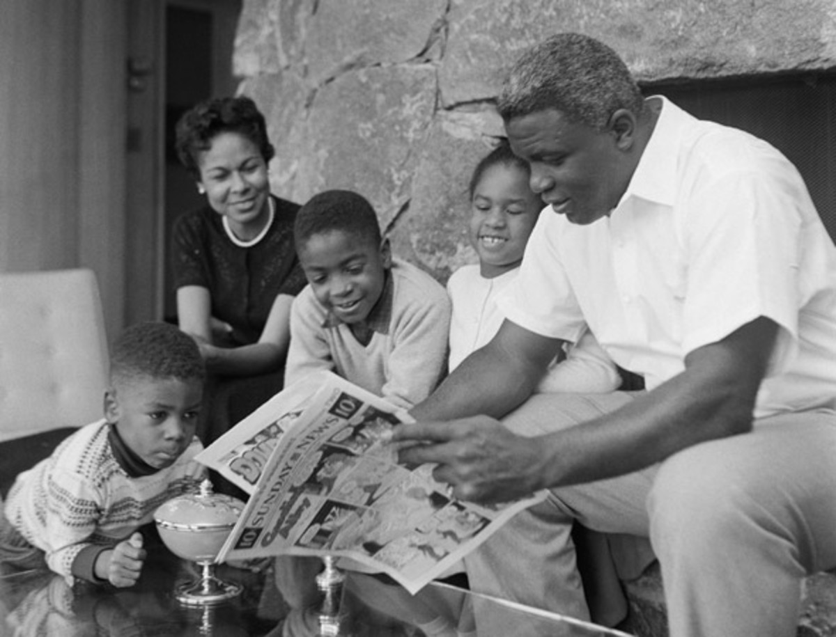 Jackie Robinson: Jackie Robinson, reported to be retiring from baseball, reads the comics to his children as his wife, Rachel, looks on in their home. The kids are, left to right: David, 4; Jackie, Jr., 10; and Sharon, 7.