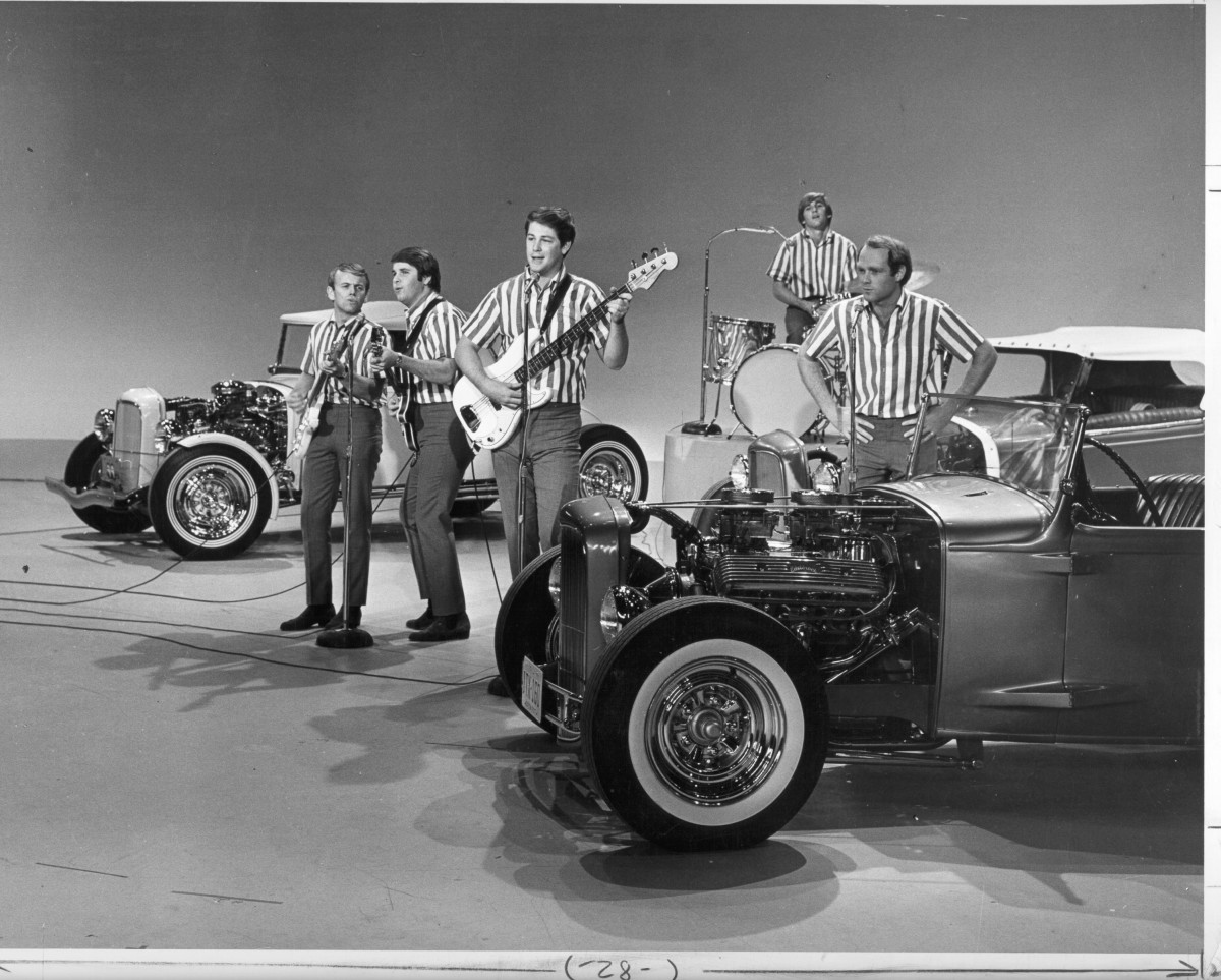 The Ed Sullivan Show Guests: Beach Boys members Al Jardine, Carl Wilson, Brian Wilson, Dennis Wilson, and Mike Love rock out amid hot rods on The Ed Sullivan Show in 1964.