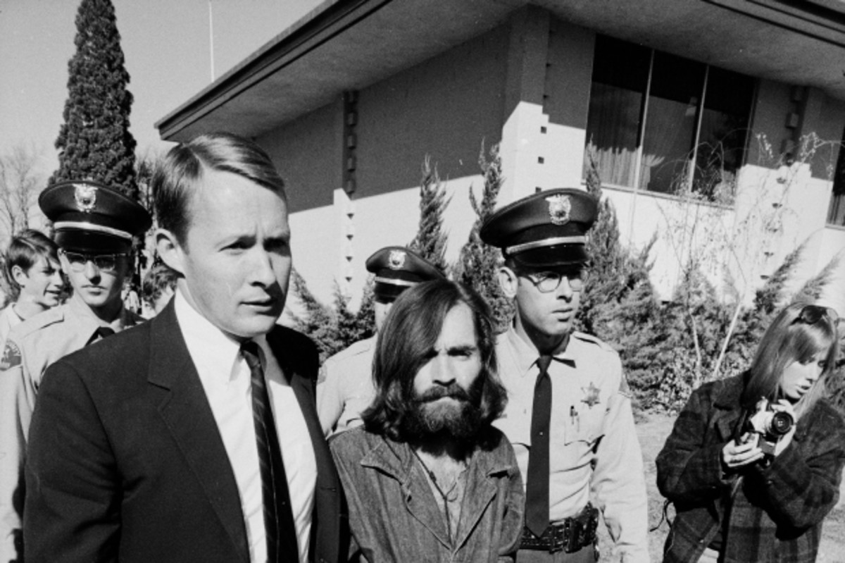 "After his arrest for the ""Tate-LaBianca murders,"" Charles Manson walks to a preliminary hearing of the case in December 1969."