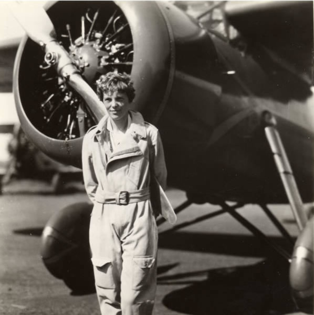Amelia Earhart: Amelia Earhart standing in front of the propellers on her plane, ca. 1935. George Palmer Putnam Collection of Amelia Earhart Papers, Courtesy of Purdue University Libraries, Karnes Archives and Special Collections.