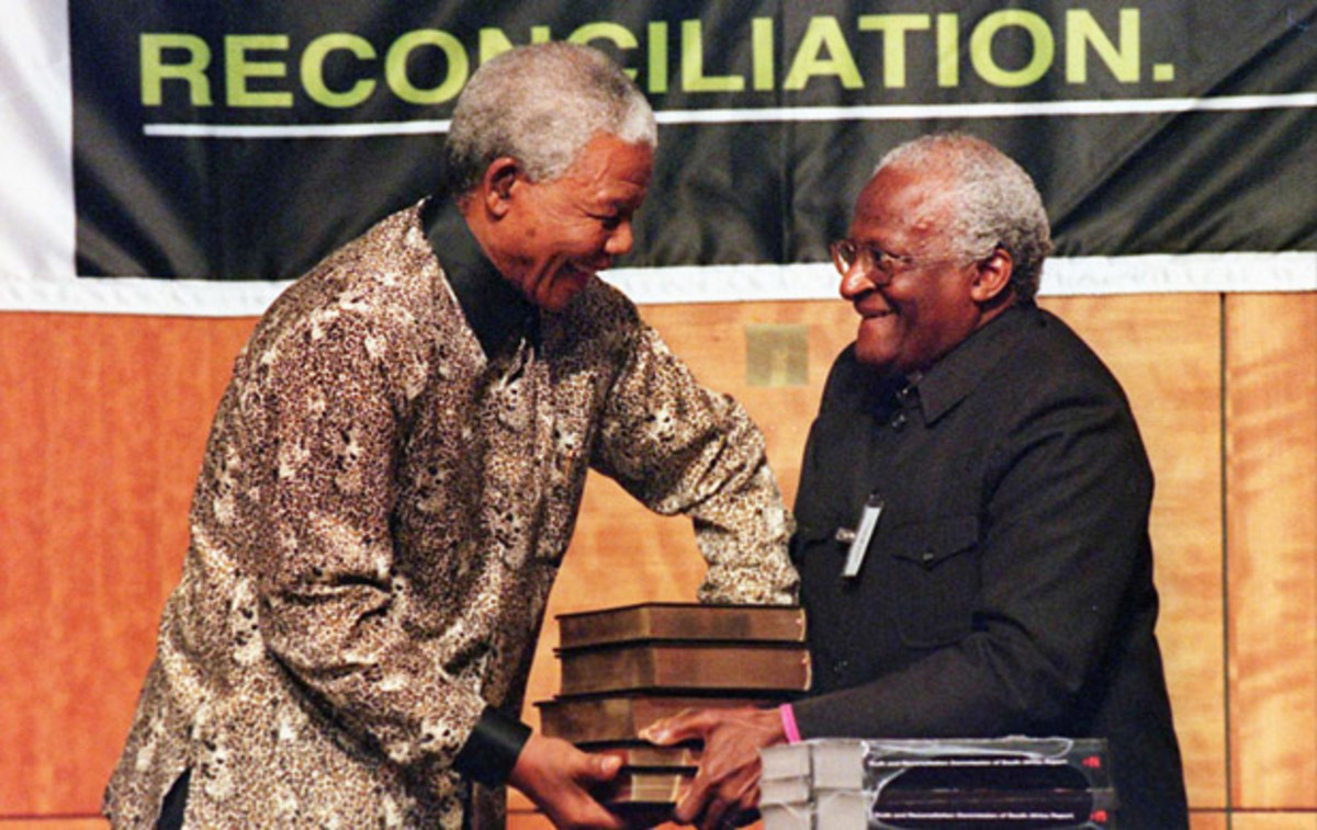 Nelson Mandela Photo Gallery: In Pretoria, South Africa, Nelson Mandela receives several volumes of the final report made by the Truth and Reconciliation Commission, a group designed to repair the damage done during the apartheid, from Archbishop Desmond Tutu on October 29, 1998. (Photo by WALTER  DHLADHLA/AFP/Getty Images)