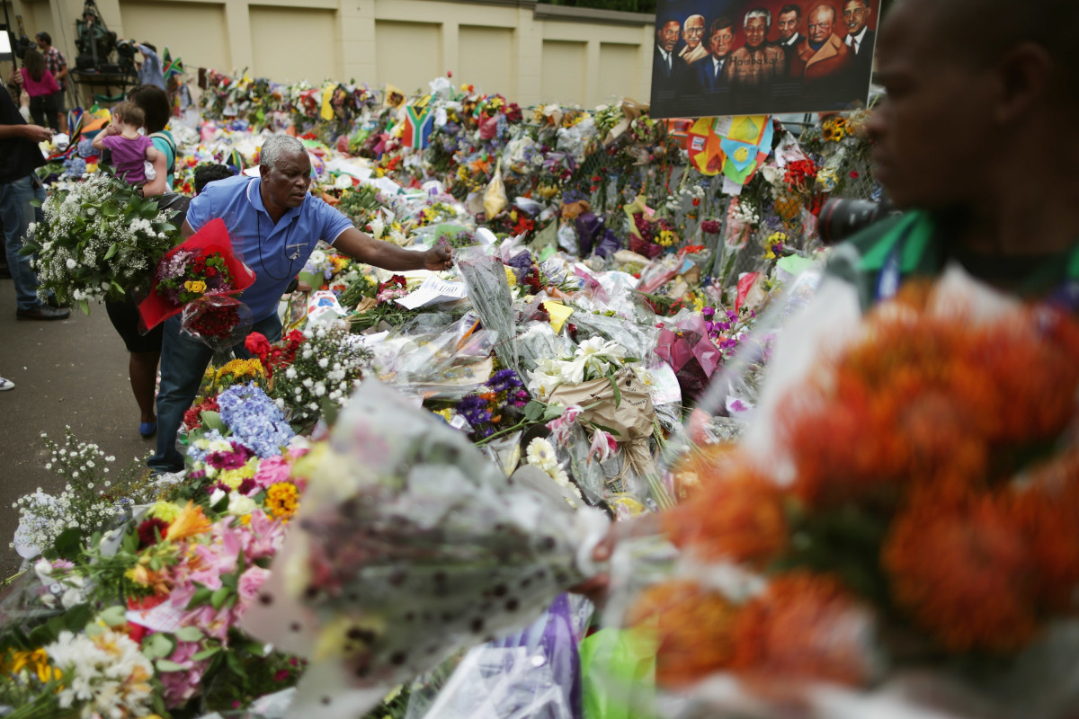 On December 9, 2013, four days after Nelson Mandela's death, thousands of South Africans pay their respects to the beloved president and longtime activist with flowers, portraits and flags, in Johannesburg, South Africa.