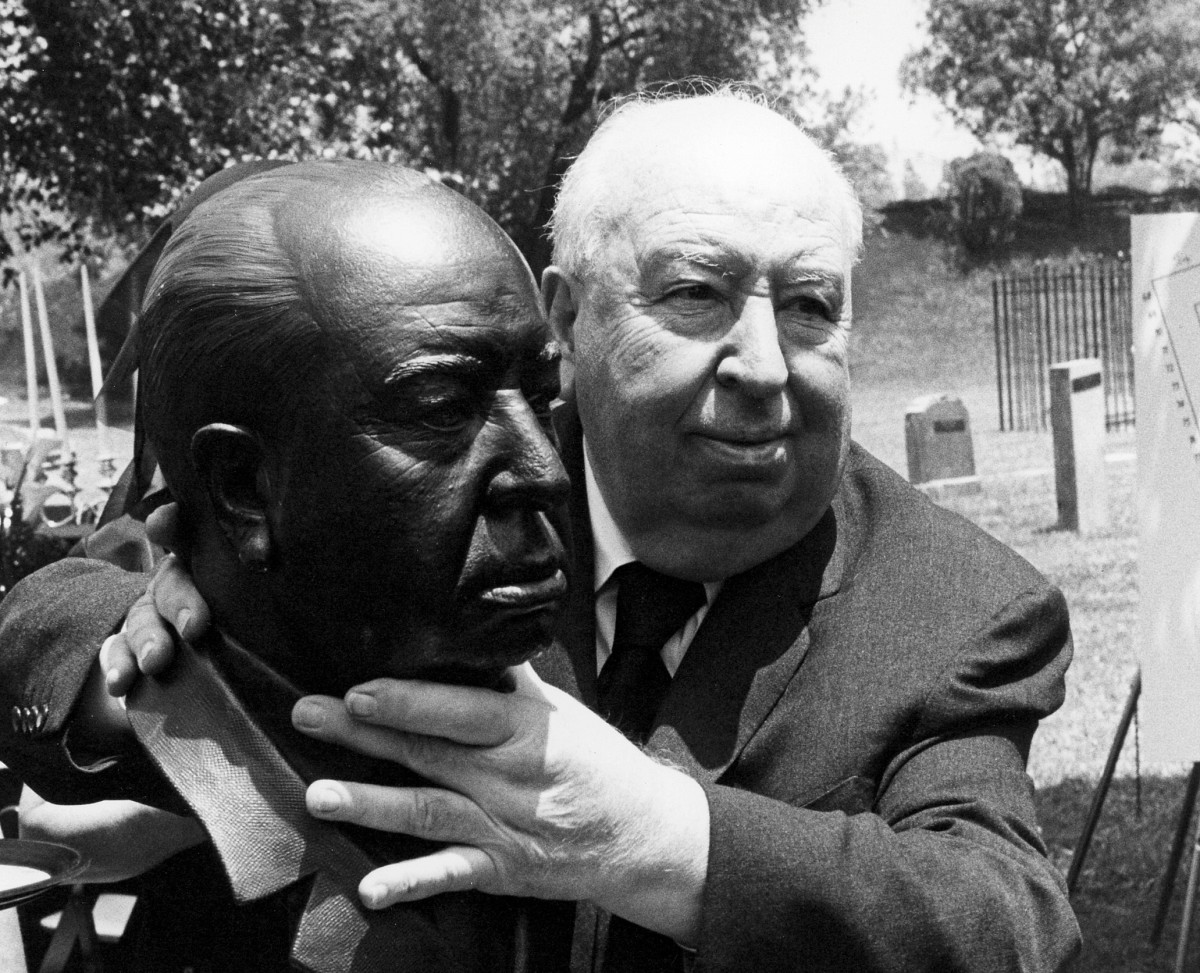 Alfred Hitchcock strangles a bust of himself on the Universal Studios lot. It's the same location where he threw a morbid lunch for the cast of Family Plot (1976), among the prop tombstones pictured in the background. (Photo: Universal Pictures/Photofest)