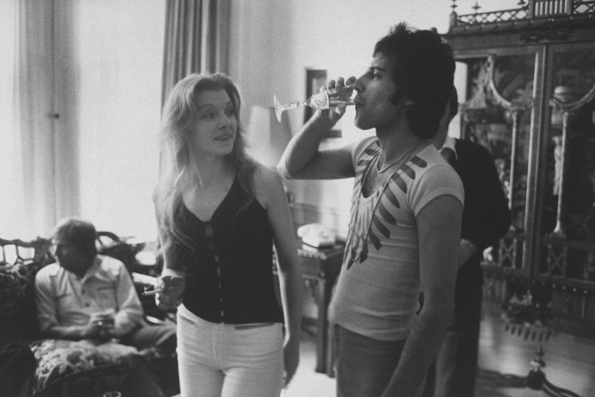 Freddie Mercury drinking a class of champagne as his girlfriend Mary Austin looks on during party for friends at home
