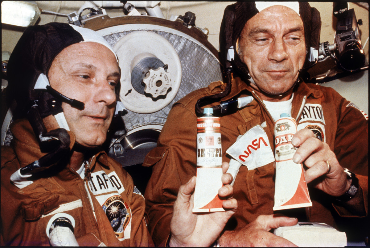 Tom Stafford and Deke Slayton holding tubes of vodka given to them by Russian cosmonauts during historic rendezvous and linkup of Apollo and Soyuz spacecraft.