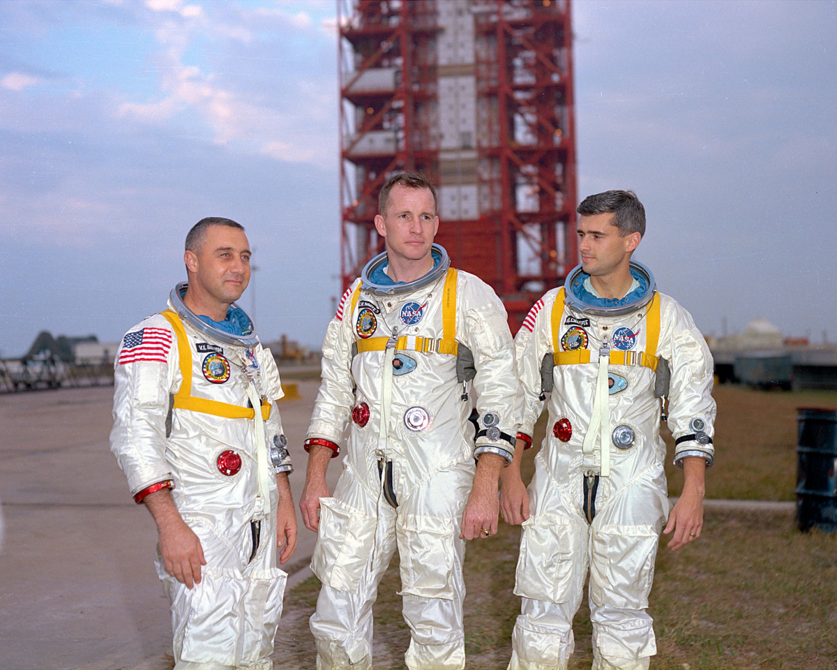 Gus Grissom, Ed White and Roger Chaffee pose in front of their Saturn 1 launch vehicle at Launch Complex 34 at the Kennedy Space Centre, Florida