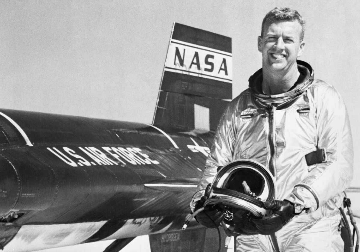 Joseph A. Walker smiles as he stands beside an X-15 rocket plane in which he flew at a record breaking altitude of 165,000 feet and a speed of 2,590 miles an hour. California.