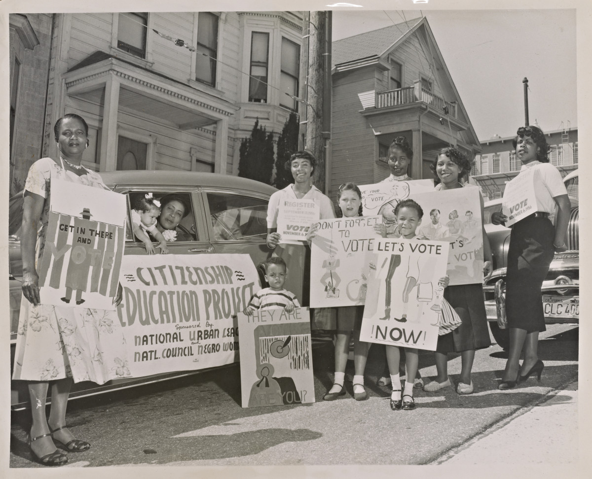 Women and children standing in front of a motorcade with signs from the Citizenship Education Project, a partnership between the National Urban League and the National Council of Negro Women.