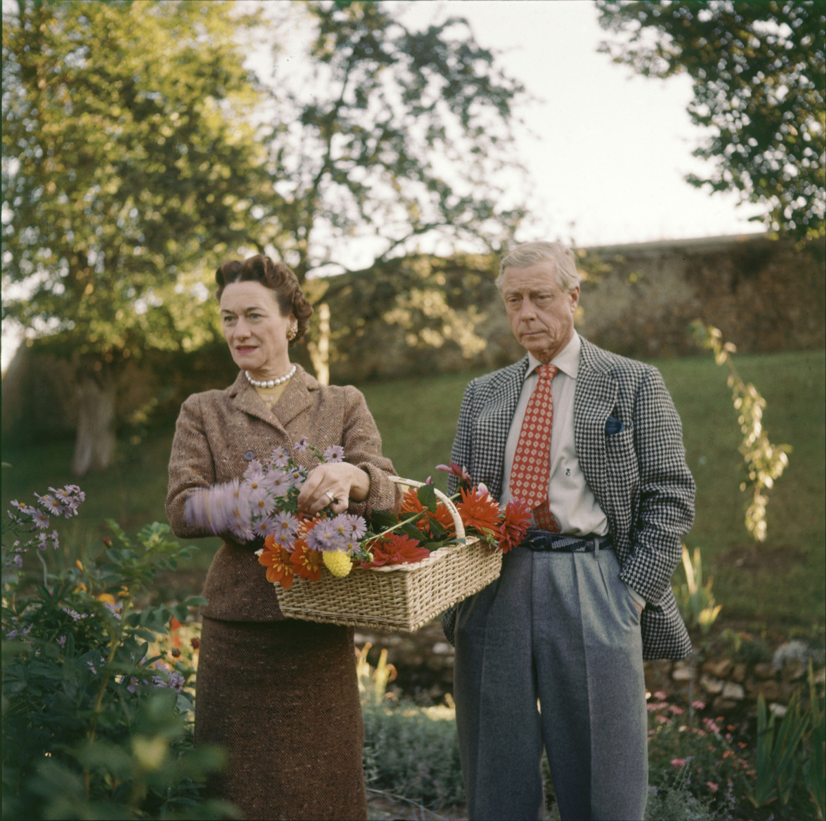 The Duchess and Duke of Windsor pick flowers on the grounds of their home, la Moulin de la Tuilerie, in the commune of Gif-sur-Yvette, outside of Paris, France, 1955.