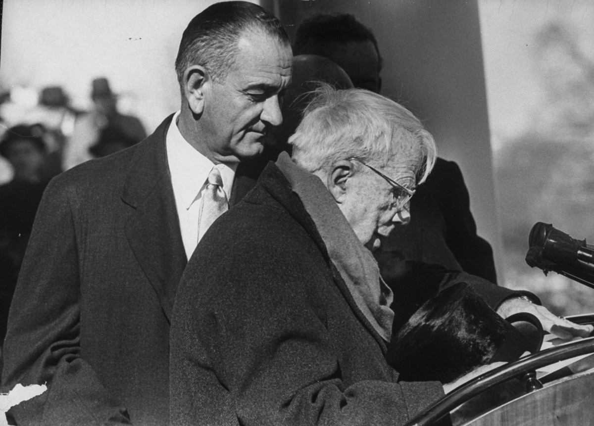 Lyndon B. Johnson assisting poet Robert Frost during the Inaugural ceremony for President John F. Kennedy