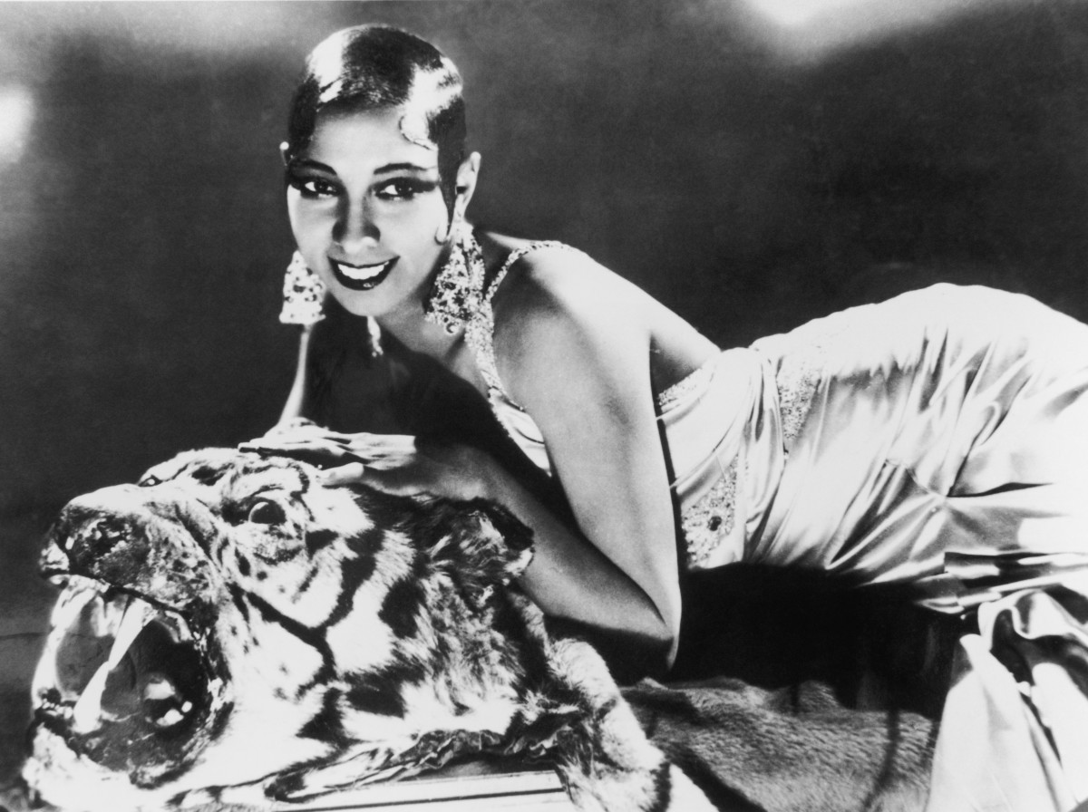 Josephine Baker lying on a tiger rug in a silk evening gown and diamond earrings