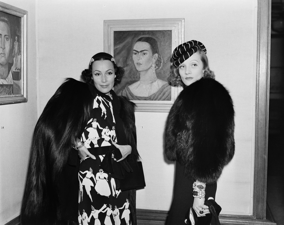 Dolores del Rio poses with actress Marlene Dietrich at a gallery featuring the paintings of Mexican artist Frida Kahlo (self portrait) in Los Angeles, California