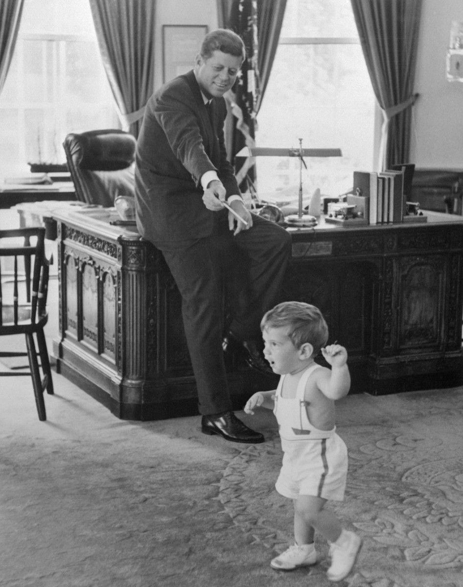 President John F. Kennedy, perched on the edge of his desk in the Oval Office, plays in the Oval Office with his toddler son, John-John.