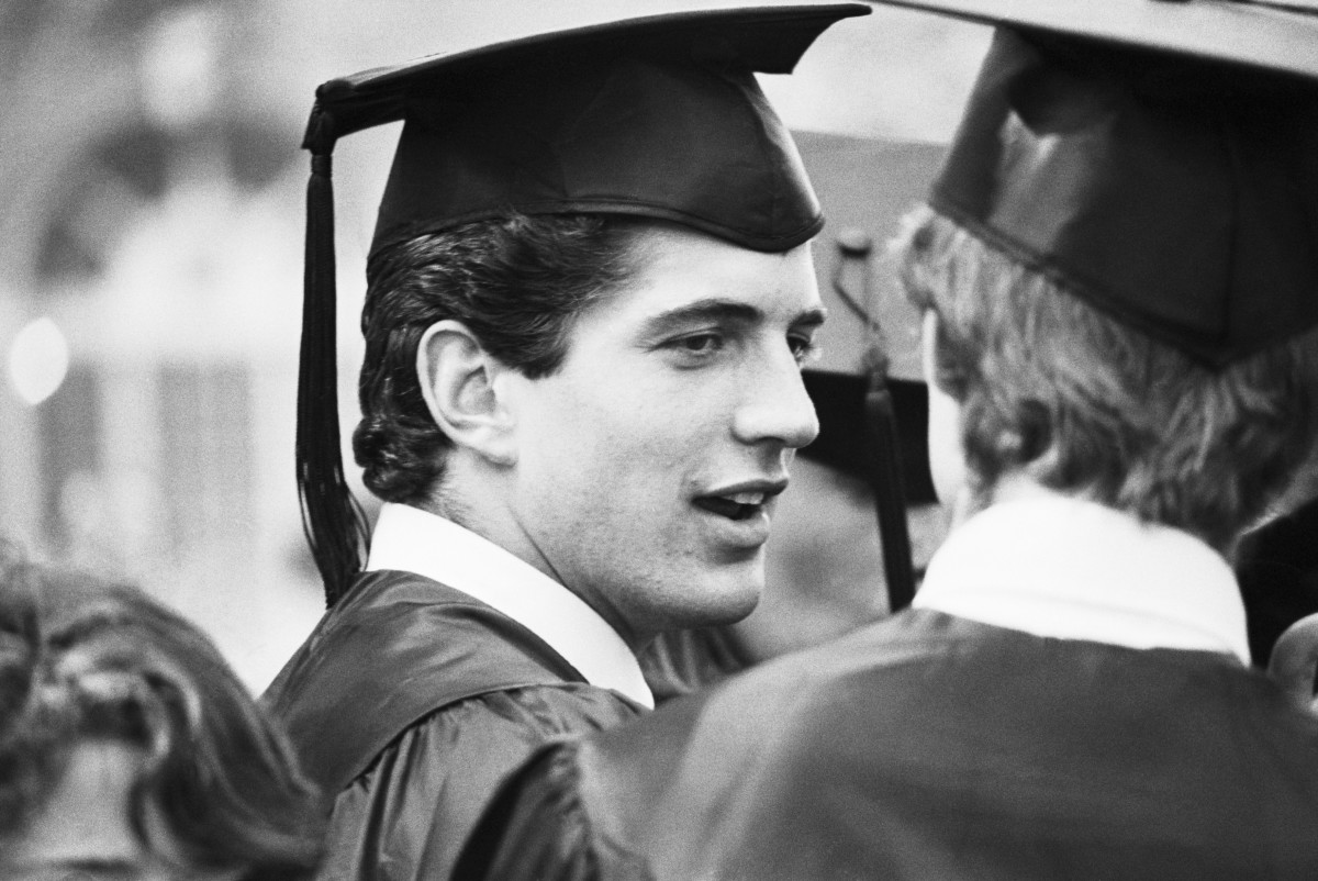 John F. Kennedy Jr., in cap and gown, chats with a classmate at his graduation ceremony at Brown University, where he received a Bachelor of Arts in History.