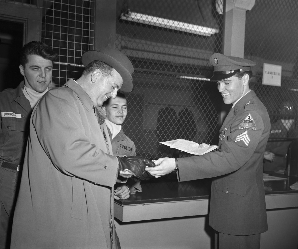 Elvis Presley grins as he hands his mustering out pay to his business manager Colonel Tom Parker