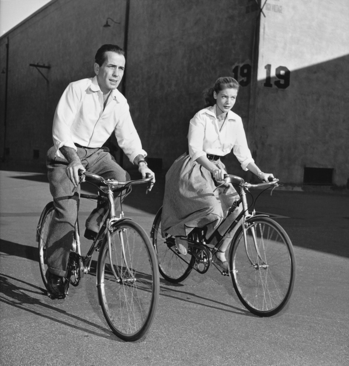 Lauren Bacall and Humphrey Bogart ride bicycles while on the set of the film 'Key Largo'