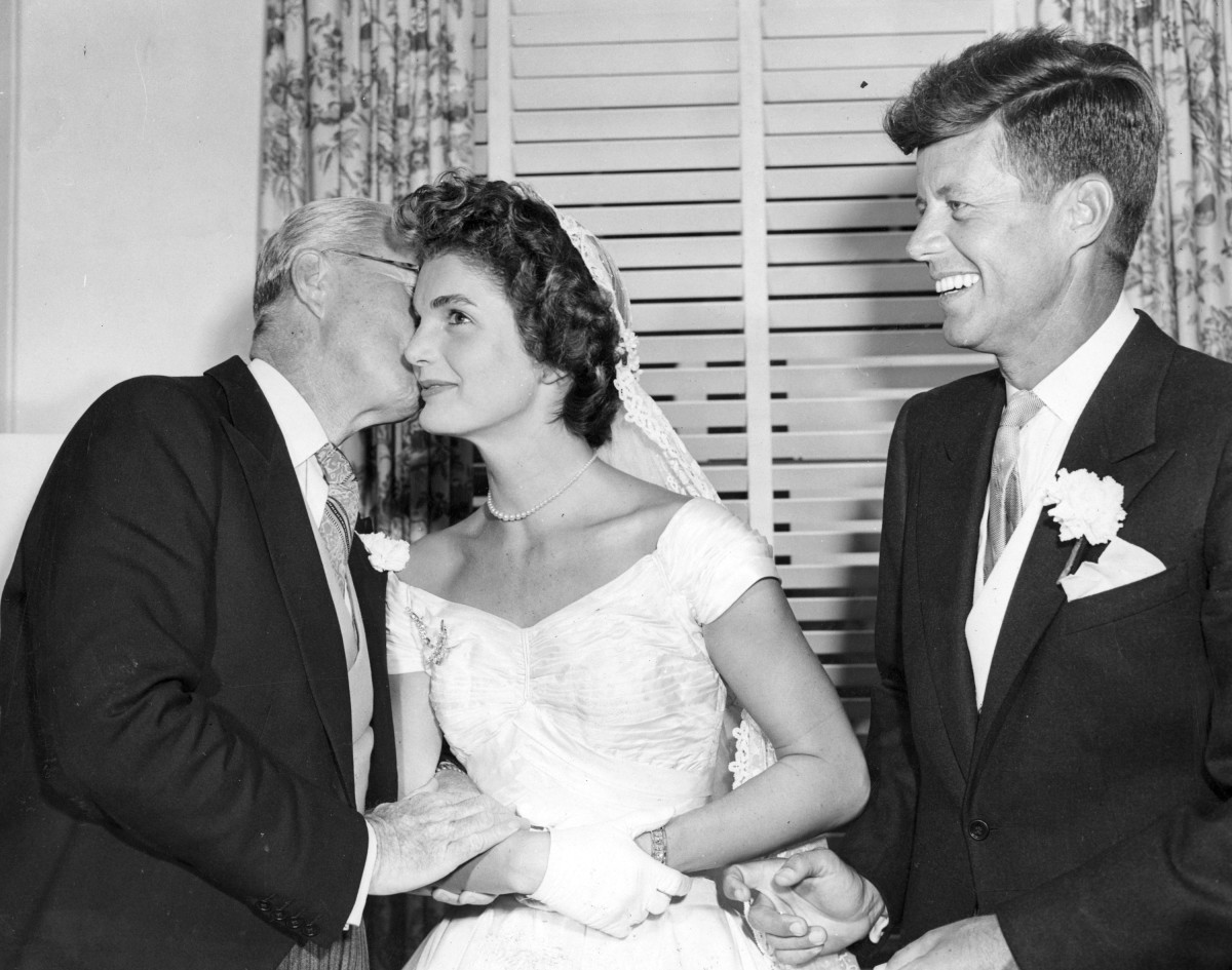 John F. Kennedy smiles as his father, Joseph P. Kennedy Sr., kisses Jackie Kennedy at the couple's wedding reception.