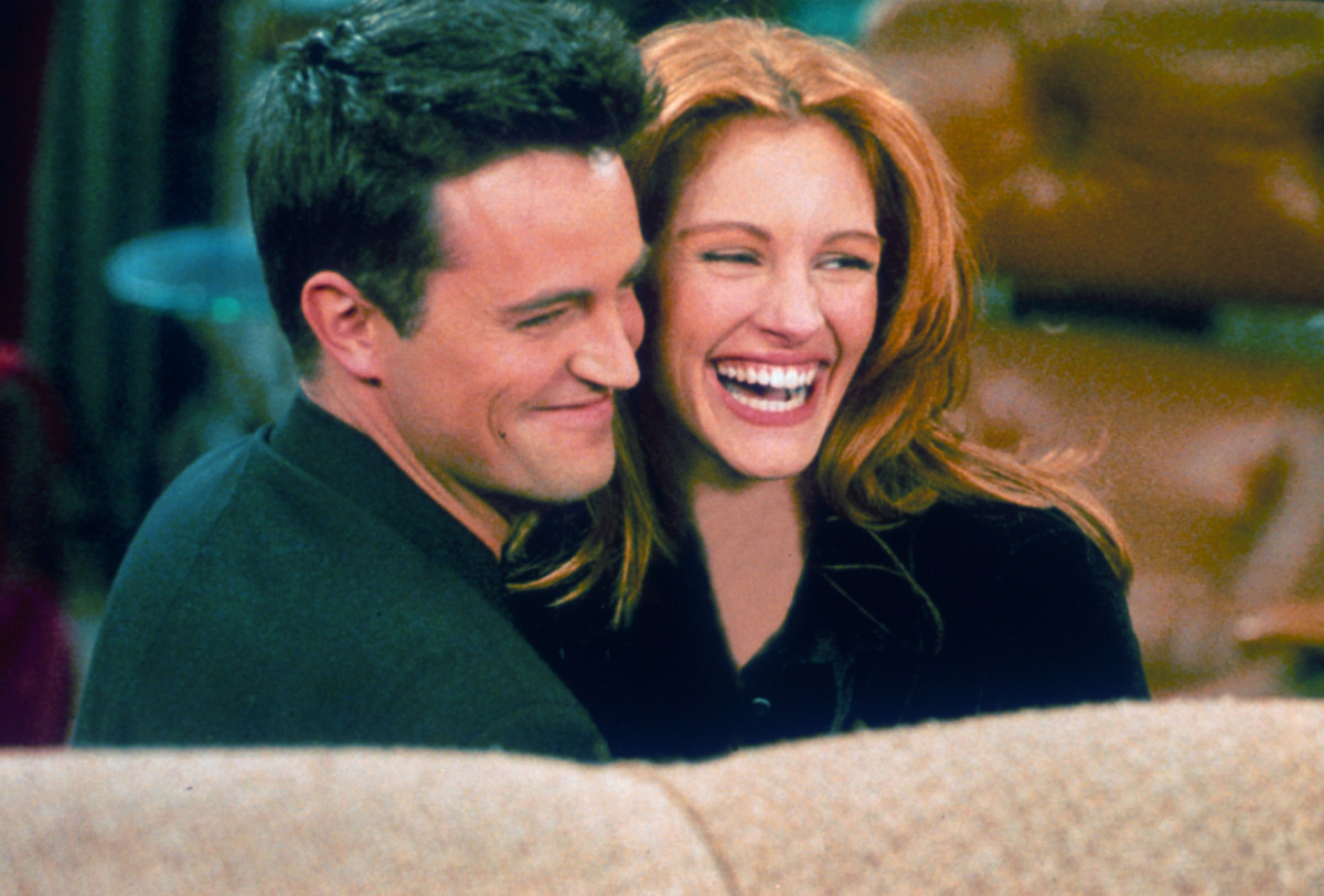 "Matthew Perry and actress Julia Roberts hug each other on the set of ""Friends."""