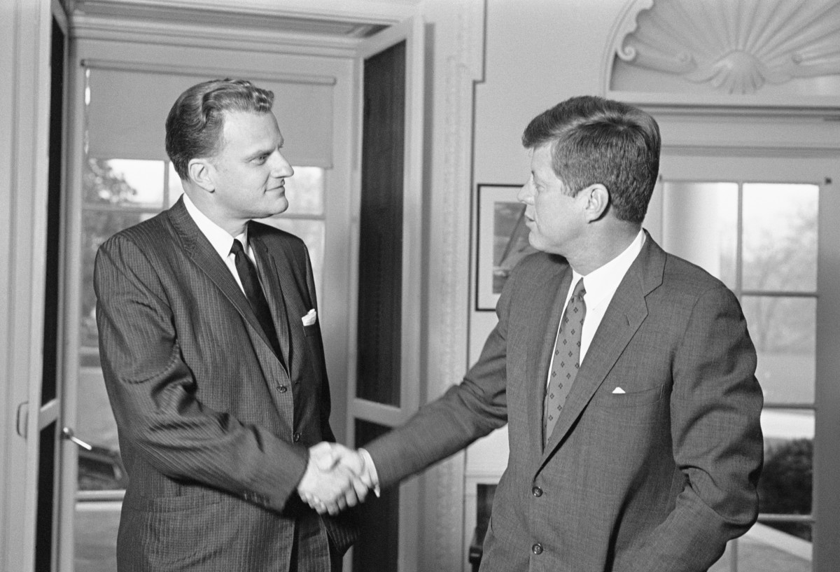 Billy Graham shakes hands with President John F. Kennedy during an unannounced visit to the White House in December 1961
