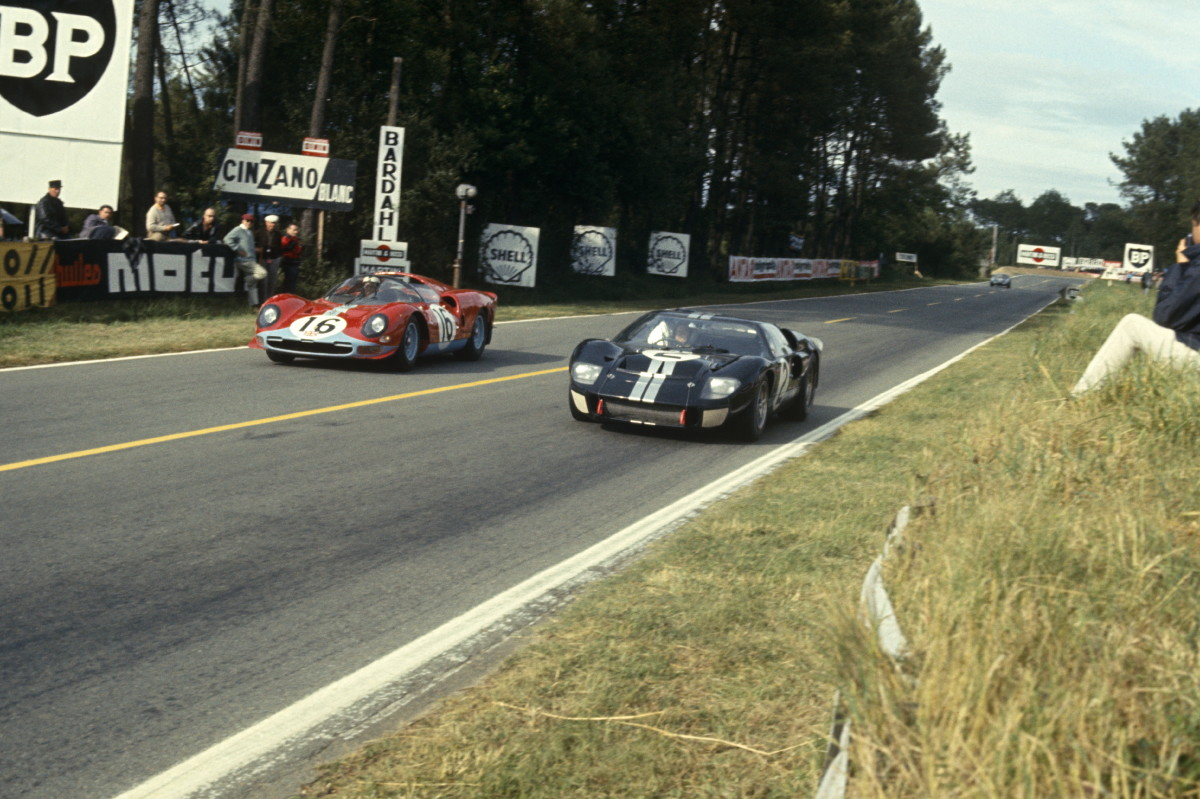 (L-R) Richard Attwood and David Piper driving a Ferrari 365 P2 Spyder (No. 16) and Bruce McLaren and Chris Amon driving a Ford Mk II (No. 2) during Le Mans on June 19, 1966
