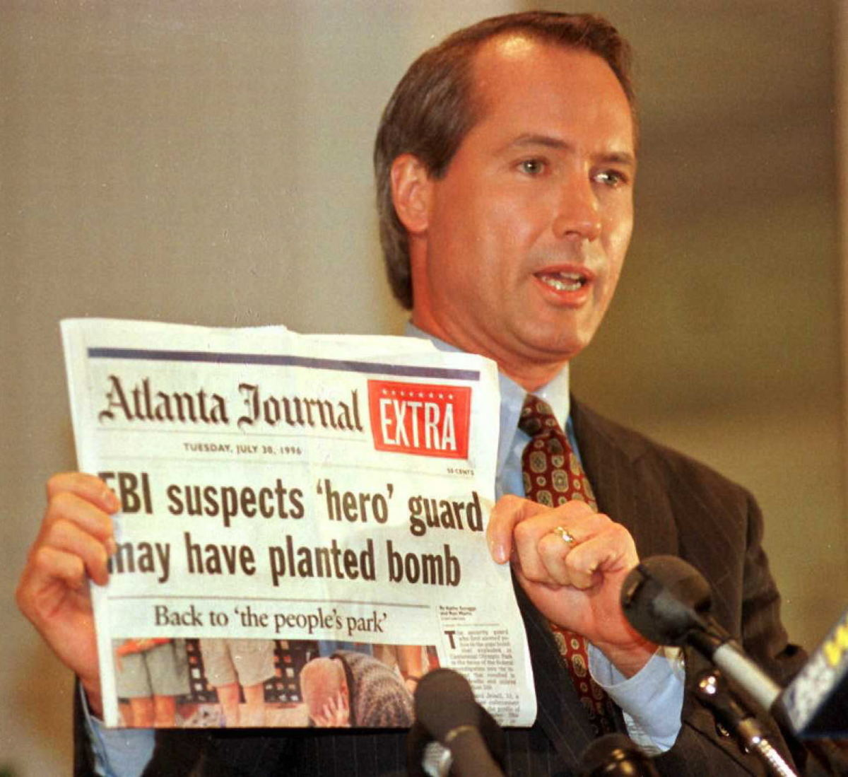 Richard Jewell's attorney Lin Wood holds a copy of the Atlanta Journal during a press conference on October 28, 1996, in Atlanta, Georgia