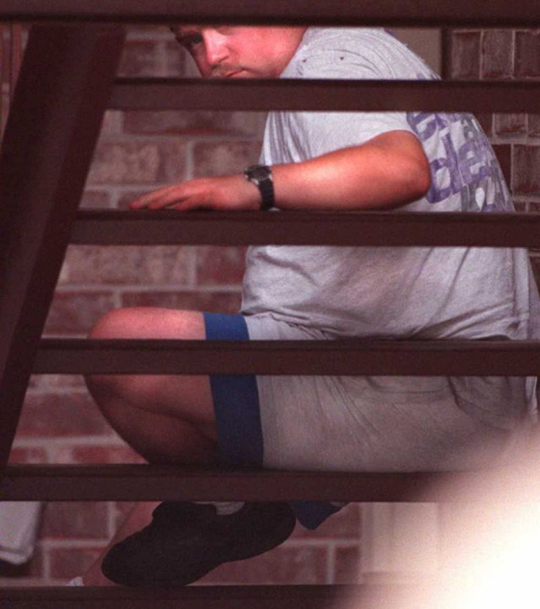Richard Jewell looks through stairs at his apartment complex while FBI and local police agents search his apartment on July 31, 1996