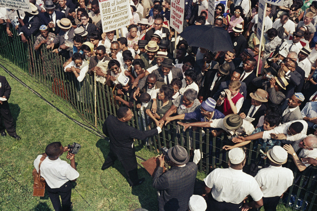 Martin Luther King Jr. shaking hands with the crowd during the March on Washington