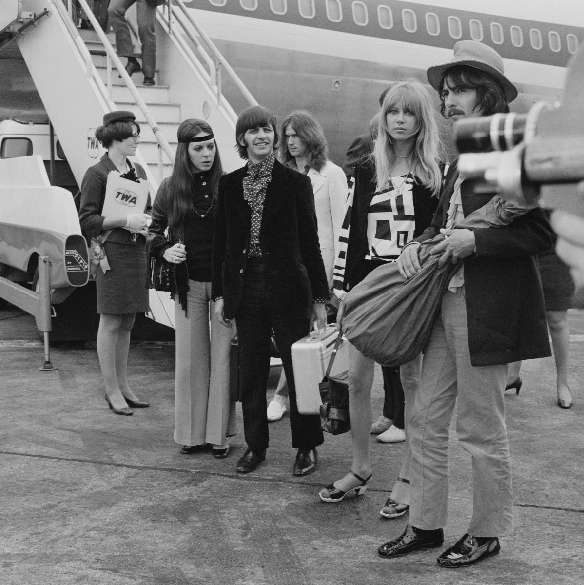 Eric Clapton (in the white suit,) Ringo Starr and his wife Maureen Cox and George Harrison and his wife Pattie Boyd at Heathrow Airport, in London on June 26, 1968