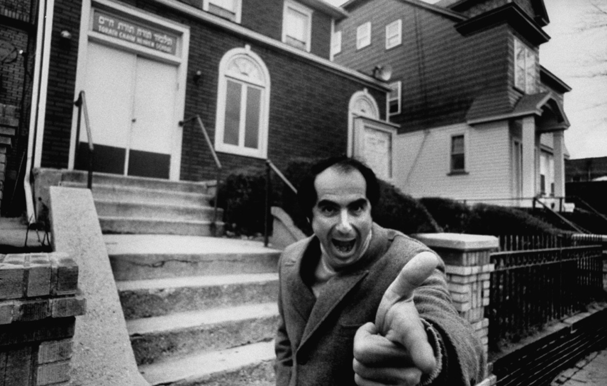 Philip Roth standing near Jewish center and Hebrew school