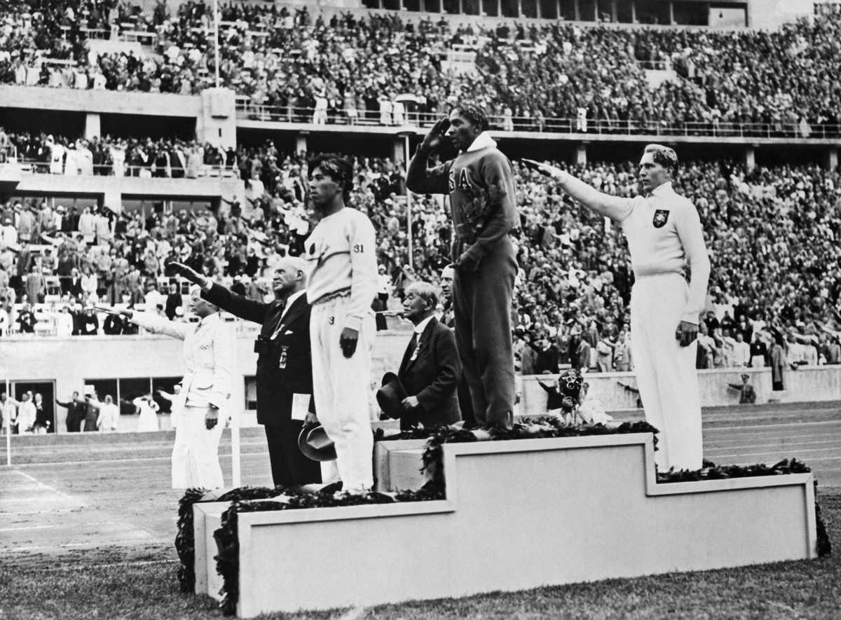 The medal winners in the 1936 long jump (from left): Japan's Naoto Tajima (bronze), American Jesse Owens (gold) who set an Olympic record in the event, and Germany's Luz Long (silver) giving a Nazi salute