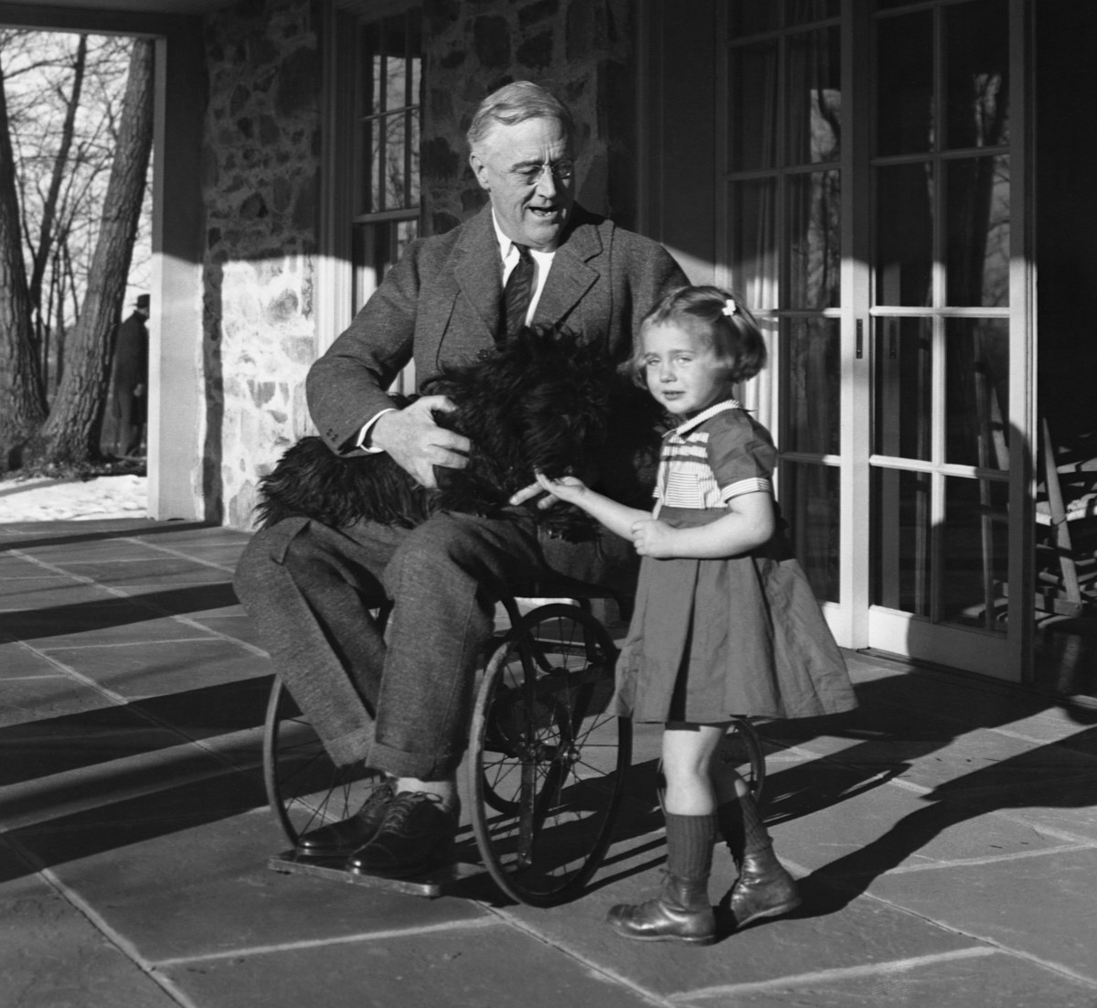 Franklin Roosevelt holds his Scotch terrier, Fala, on his lap as he talks to Ruthie Bie, the daughter of the Hyde Park caretaker