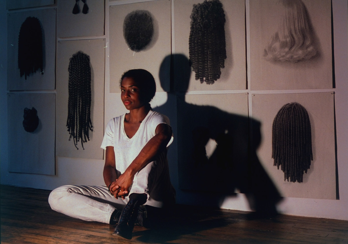 Lorna Simpson sitting on the floor in her studio in front of her installation Wigs