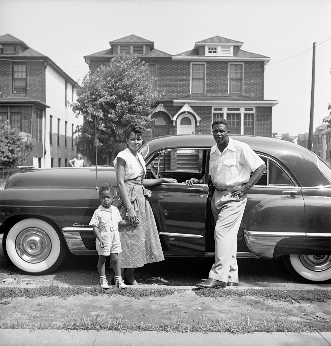 Jackie Robinson, his wife Rachel and their son Jackie Jr. posing by their car in Brooklyn, New York in July 1949.