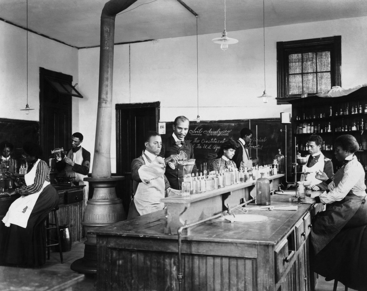 George Washington Carver with students in his laboratory at Tuskegee Institute