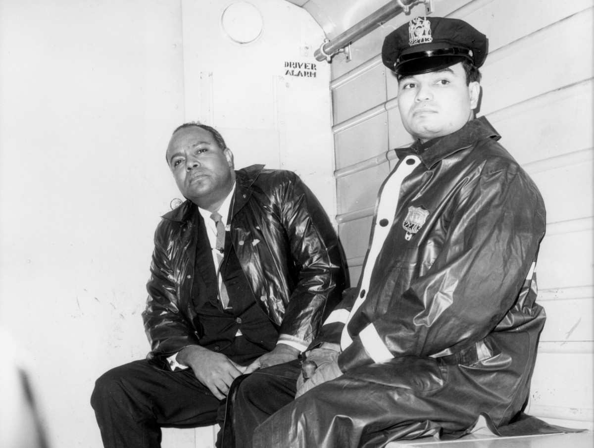 James Farmer, the Executive Director of the Congress for Racial Equality, sits next to a uniformed officer in the back of a police wagon