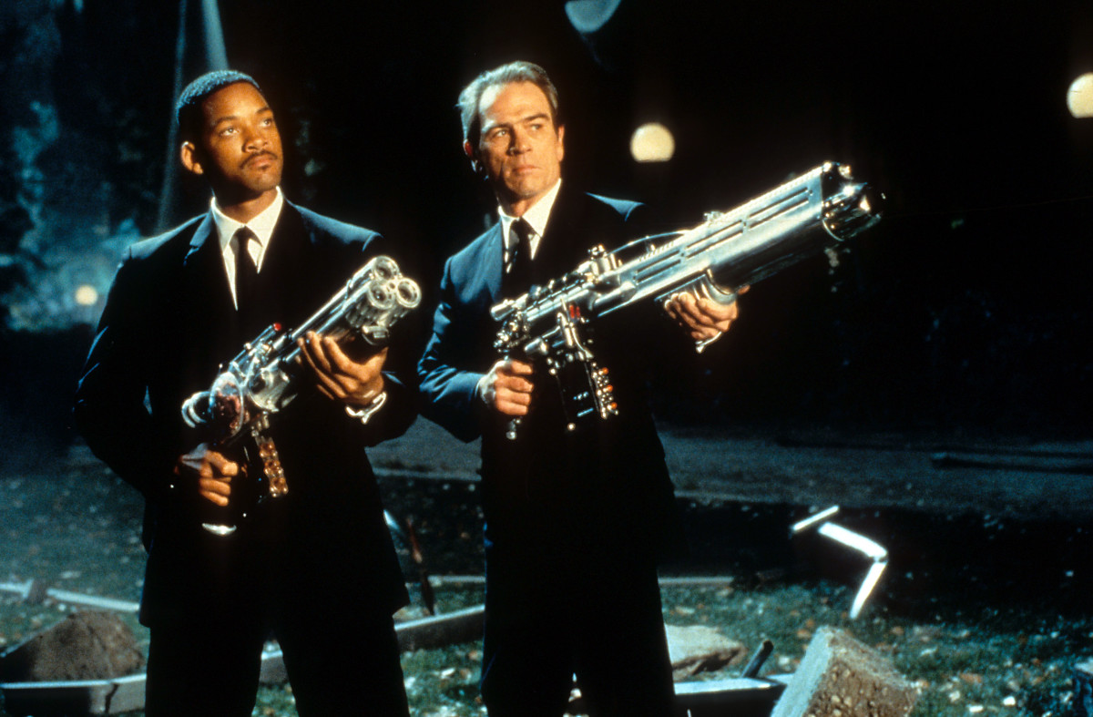 Will Smith and Tommy Lee Jones aiming their weapons towards the sky in a scene from the film 'Men In Black', 1997