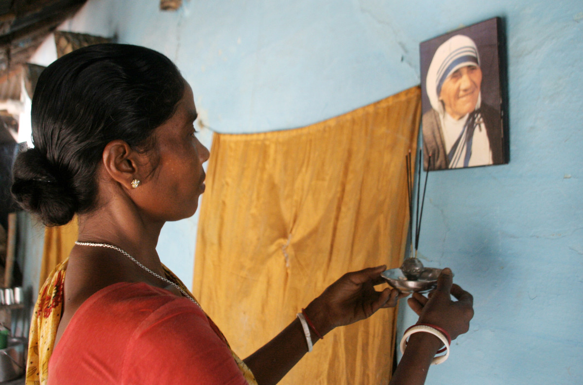 Monica Besra prays in front of a picture of Mother Teresa at her home village of Nakur in Danogram