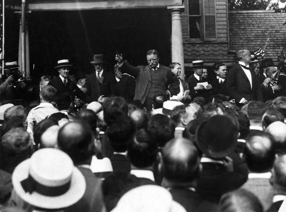 Theodore Roosevelt gestures to make a point as he addresses a crowd from the steps of Sagamore Hill