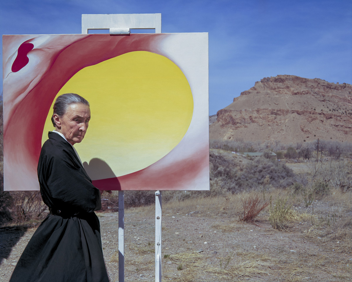 Georgia O'Keeffe poses outdoors beside an easel with a canvas from her series, 'Pelvis Series Red With Yellow,' in Albuquerque, New Mexico, 1960