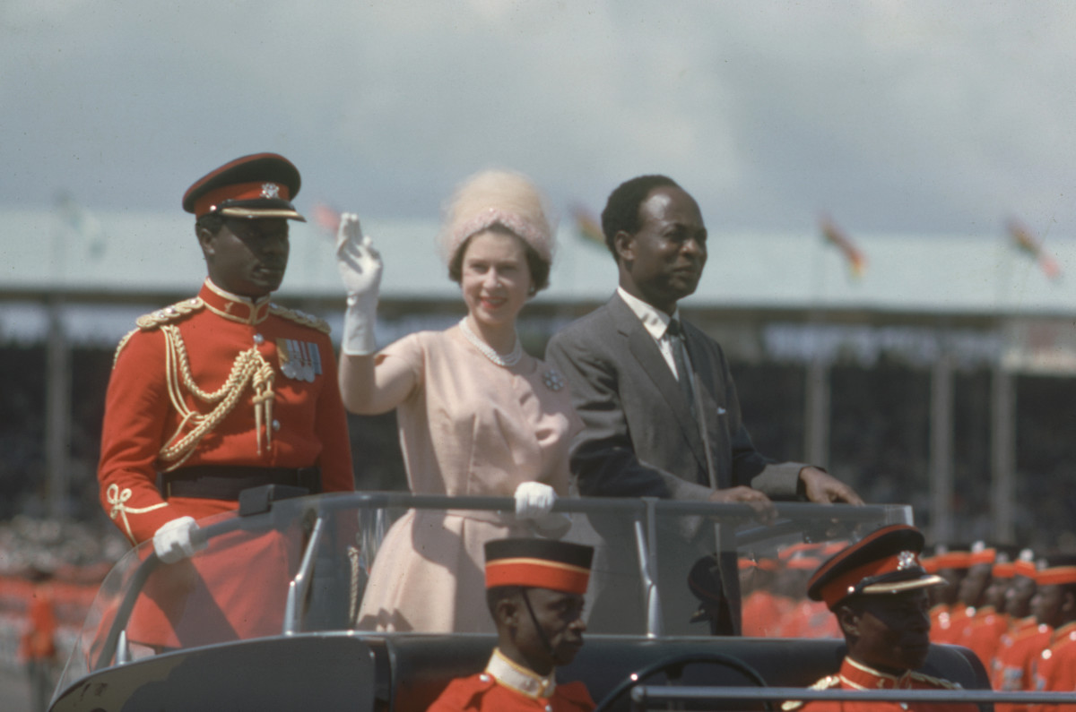 Queen Elizabeth II waves to spectators as she and President of Ghana Kwame Nkrumah drive into Black Star Sqaure in an open top car, Accra, Ghana, November 9, 1961.