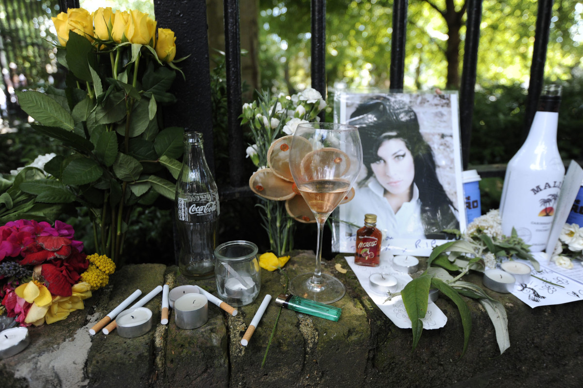 Cigarettes, alcohol and photos are left with flowers and messages on July 24, 2011, near the house in north London where the body of Amy Winehouse was found the previous day