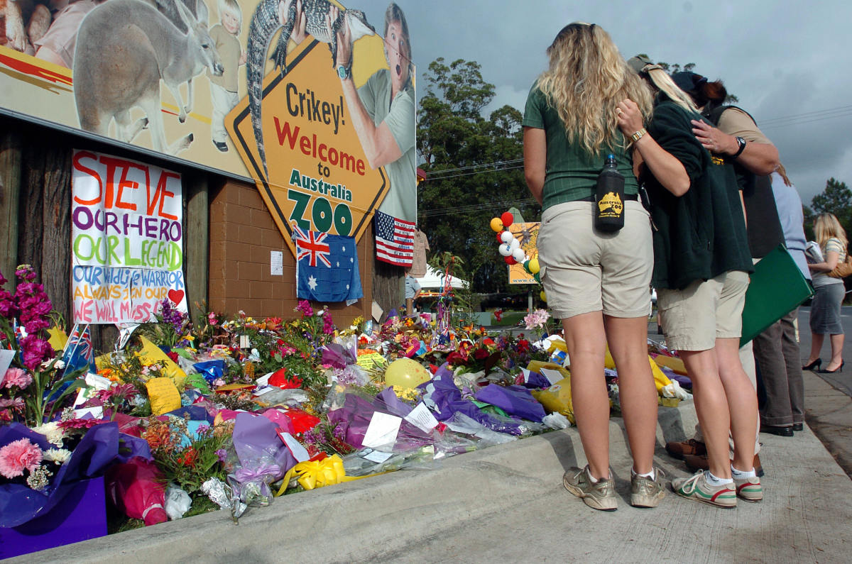 Staff members from the Australia Zoo console each other as they observe tributes outside the zoo on September 6, 2006, following the death of Steve Irwin