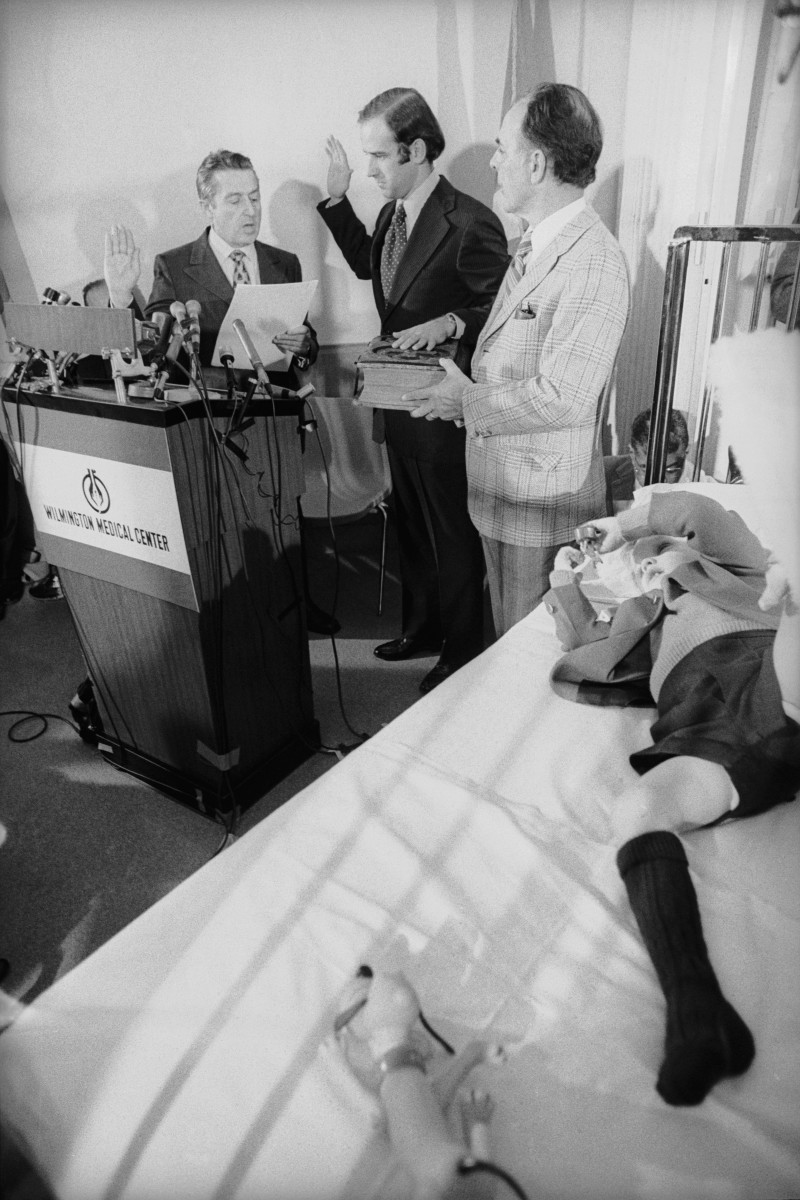 Joe Biden takes the oath of office from U.S. Senate secretary Frank Valeo with his father-in-law, Robert Hunter, and son Beau at his side, in Beau's hospital room