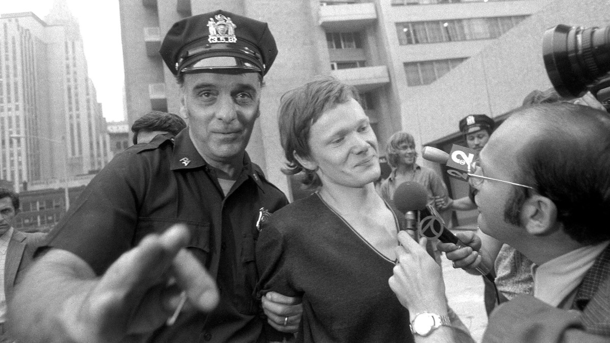 Philippe Petit answers reporter's questions as he is escorted from Beekman Hospital by Port Authority police officer, after being arrested for walking a tightrope between the two towers of the World Trade Center.
