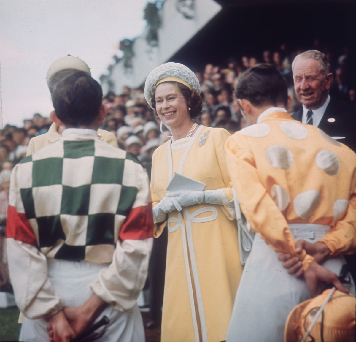 Queen Elizabeth II chats with jockeys Ron Quinton and Hilton Cope before the Queen Elizabeth Stakes at Randwick racecourse near Sydney, during her tour of Australia on April 1, 1970