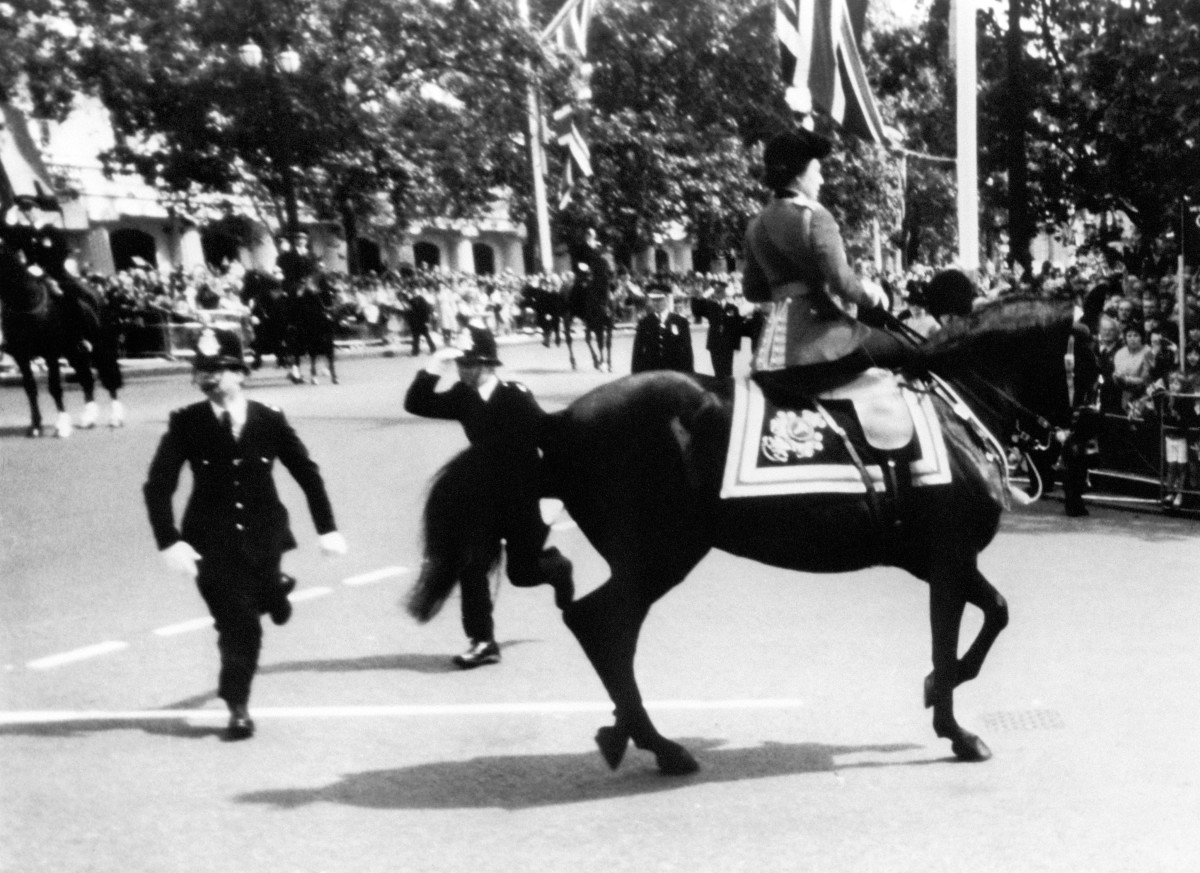 Queen Elizabeth II calms her horse while policemen spring to action after shots were heard as she rode down the mall