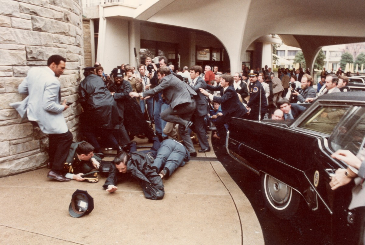Police and Secret Service agents diving to protect President Ronald Reagan amid a panicked crowd during an assassination attempt by John Hinckley Jr. outside the Washington Hilton Hotel in Washington, D.C. on March 30, 1981