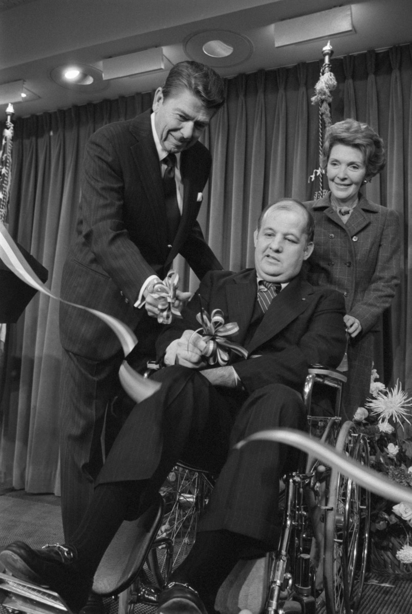 Press Secretary Jim Brady, with Ronald and Nancy Reagan, cuts the ribbon opening the renovated press center at the White House in November 1981