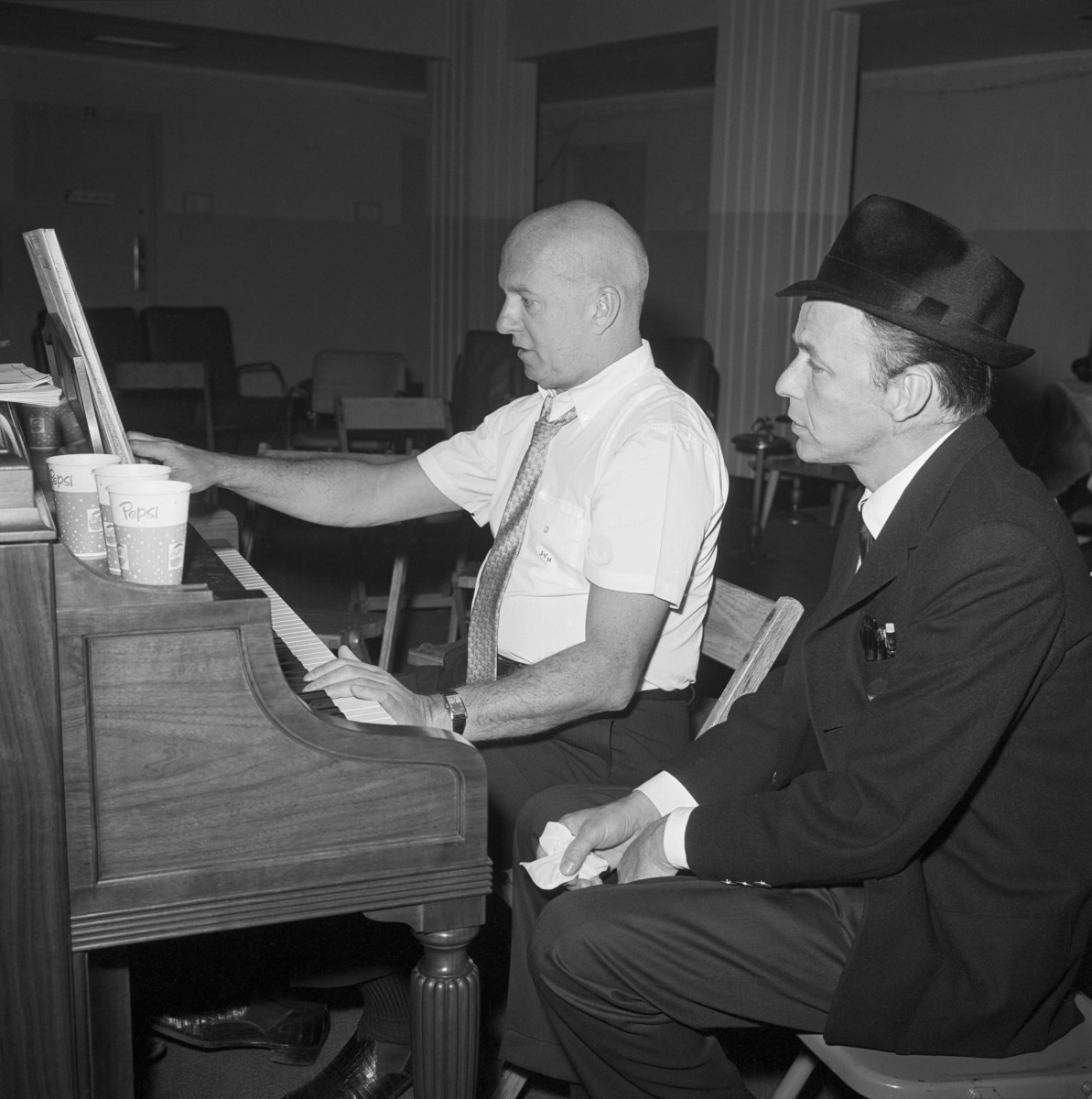 Frank Sinatra sits beside songwriter Jimmy Van Husen at the piano during rehearsal for the inaugural gala